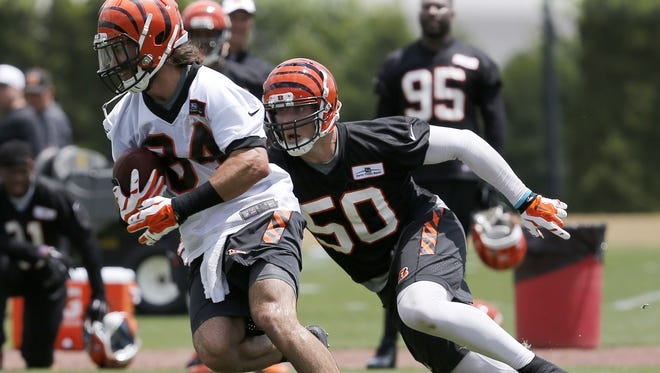 New Bengals linebacker A.J. Hawk, right, let a fan know just how hard he can hit at a golf tournament.