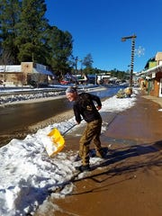 Happy Hiker owner Rich Dozier shovels the storm's bounty from the sidewalk in front of his shop in midtown Ruidoso.