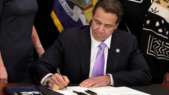 New York Gov. Andrew Cuomo signs a law that will gradually