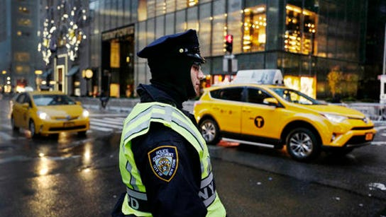 A New York City police officer stands watch outside