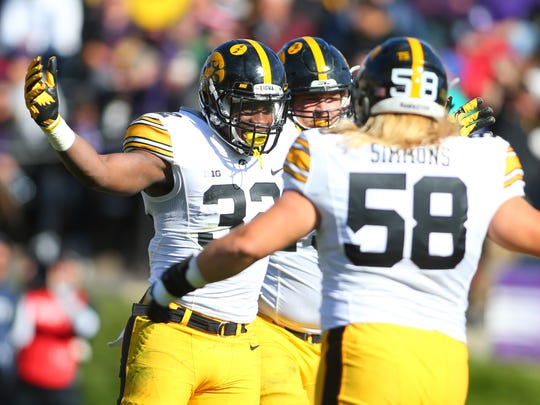 Iowa running back Derrick Mitchell Jr. (32) celebrates with offensive lineman Eric Simmons (58) after scoring a touchdown during the second half of the game at Ryan Field.