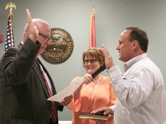 Robertson County Mayor Howard Bradley administers the oath of office to Scott Rice while his sister, County Commissioner Stacey Moore assists.