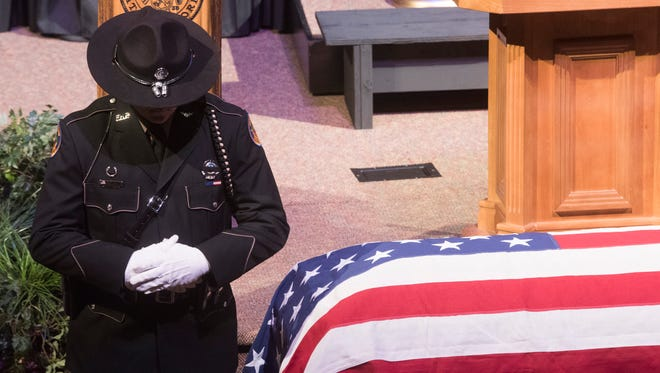 A law enforcement officer pays his respects during a funeral service for former state Sen. Greg Evers on Tuesday, Aug. 29, 2017, at First Baptist Church of Milton.