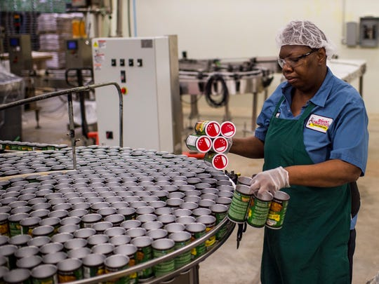 A worker places empty seasoning cans onto a turntable into the packaging area of the production facility at Tony Chachere's Cajun Foods in Opelousas, La., Monday, March 23, 2015.