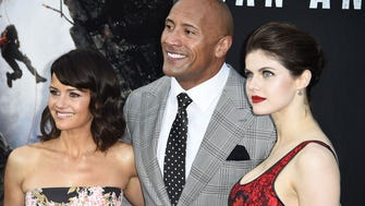 """The Rock rolled into the """"San Andreas"""" Hollywood premiere on a fire truck Tuesday night. He only added to the heat with co-stars Carla Gugino (L) and Alexandra Daddario (R)."""