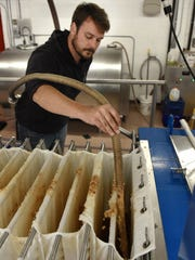 Parmenter's employee Aaron Gierada pours the crushed