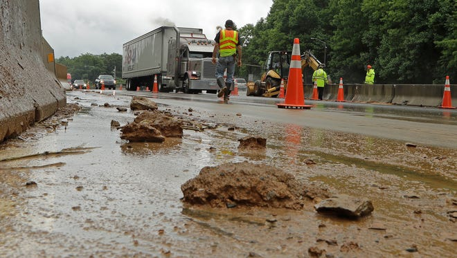 Workers block off lanes of I-40 near Old Fort, N.C., May 30, 2018 after heavy rains from the fringes of Subtropical Storm Alberto caused a mudslide Tuesday evening.
