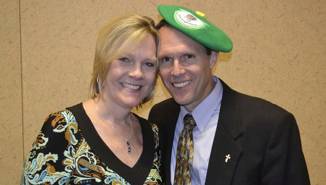 Wearing the traditional green beret that goes to the winner of the De Pere Community Silver Knight Award, Kevin DeCleene stands with his wife JoDee after Monday night's ceremony at Swan Club in De Pere.