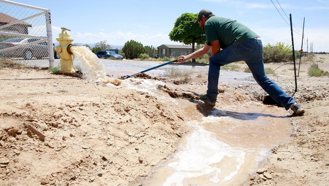 Daryl Gore of the Flora Vista Mutual Domestic Water Association opens a fire hydrant to help flush the AV Water system in July in Crouch Mesa.