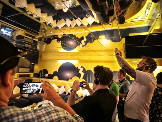 Elvis fans record their experience in Elvis' basement TV room while visiting Graceland on Friday, June 23, 2017.