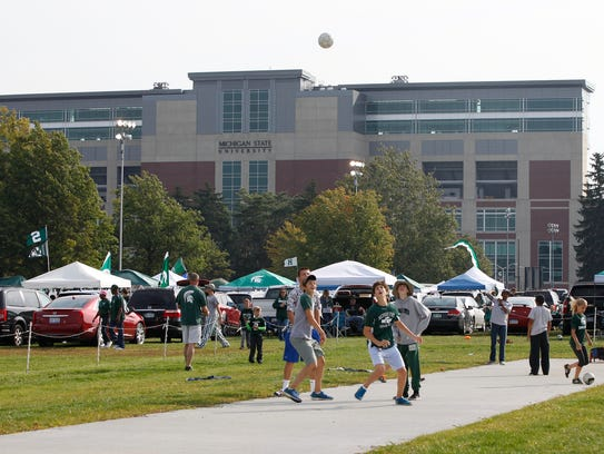 Young kids play in a field while tailgating in 2014
