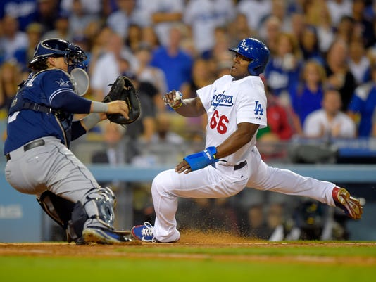 Los Angeles Dodgers' Yasiel Puig, right, scores on a sacrifice fly by Matt Kemp as San Diego Padres catcher Yasmani Grandal, tries to get to a throw that came in off line from center fielder Abraham Almonte during the third inning of a baseball game, Wednesday, Aug. 20, 2014, in Los Angeles. Almonte was charged with an error on the throw. (AP Photo/Mark J. Terrill)
