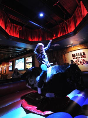 Alecia Nafziger of Arkansas has some fun riding the mechanical bull inside the Cadillac Ranch in downtown Indianapolis.