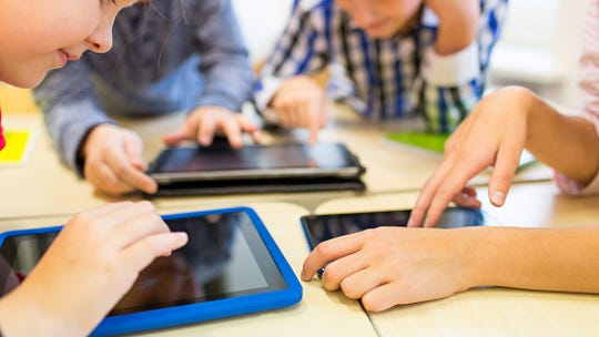 Close up of school kids playing with tablets.
