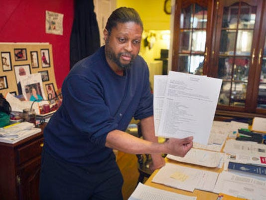 Sinhue Johnson holds up a Family Group Plan Recommendation by family court for his adolescent son, saying the recommendation states that his son is developing appropriately. (PAUL KUEHNEL - YORK DAILY RECORD/SUNDAY NEWS)