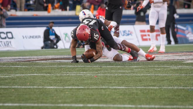 UC wide reciever Chris Moore is tackled in the fourth quarter, while spirits fell from UC players, who were behind 16 points to Virgnia Tech at the beginning of the fourth quarter. The Bearcats lost 33-17 against Virginia Tech at the 2014 Military Bowl game.