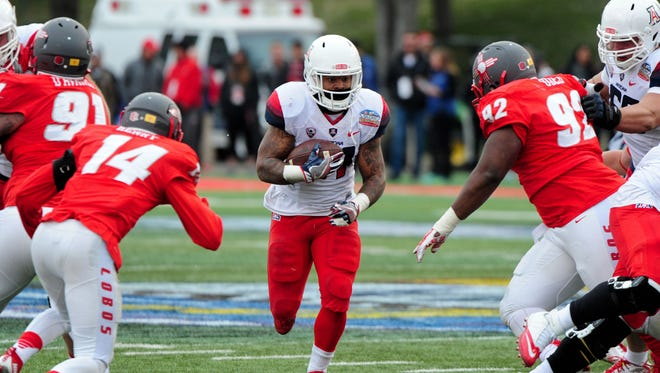 Dec 19, 2015: Arizona Wildcats running back Orlando Bradford (21) runs the ball as New Mexico Lobos safety Daniel Henry (14) and defensive lineman William Udeh (92) defend during the second half in the 2015 New Mexico Bowl at University Stadium.