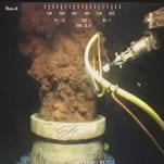 In this July 12, 2010 image, oil flows out of the top of the transition spool at the site of the Deepwater Horizon oil spill.