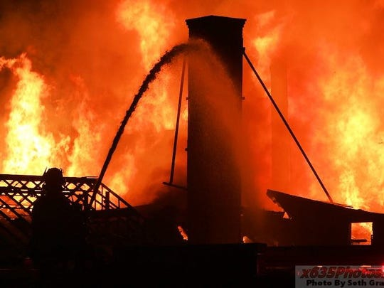 Firefighters battle a blaze at the Sprainbrook Nursery in Greenburgh Sunday, Sept. 27, 2015.