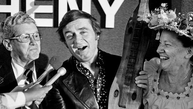 Mike Douglas, center, shows off the Tennessee dulcimer he receives from Grand Ole Opry stars Roy Acuff, left, and Minnie Pearl after arriving in Nashville April 24, 1975. Douglas is here to tape five talk shows featuring country music stars and will appear on the Grand Ole Opry.