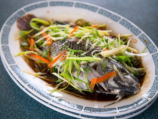 A whole steamed tilapia is smothered with ginger and