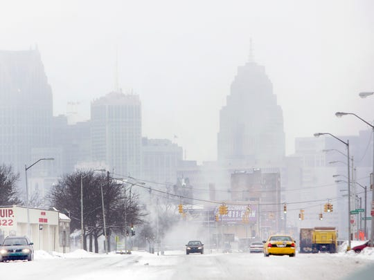 The Detroit skyline is seen through the snow and haze down Gratiot Ave. as the metro area is hit with snow and freezing rain on Tuesday, March 3, 2015.