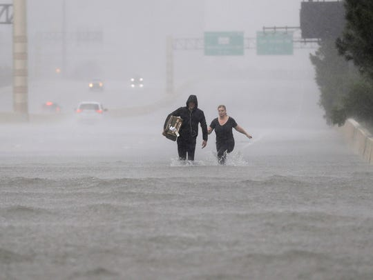 Two people walk down a flooded section of Interstate