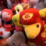 In this Feb. 12, 2015 photo, a woman shops toy sheep for Lunar New Year decorations in Beijing, China.