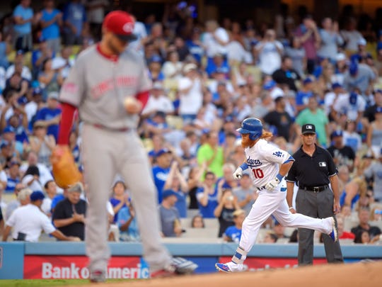 Los Angeles Dodgers' Justin Turner, right, rounds third after hitting a solo home run as Cincinnati Reds starting pitcher David Holmberg stands near the mound during the third inning of a baseball game, Saturday, Aug. 15, 2015, in Los Angeles.