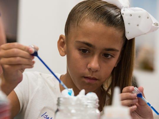 Isabella Custer, 11, of New Church, uses food coloring