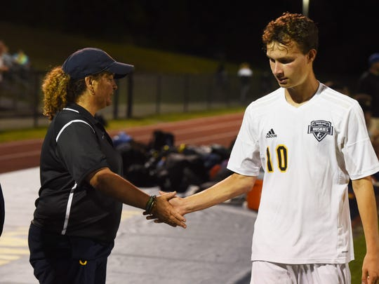 Terri Cilento, left, coach for Highland High School's varsity boys soccer team, high-fives a player during a game against Wallkill on Oct. 5, 2017.
