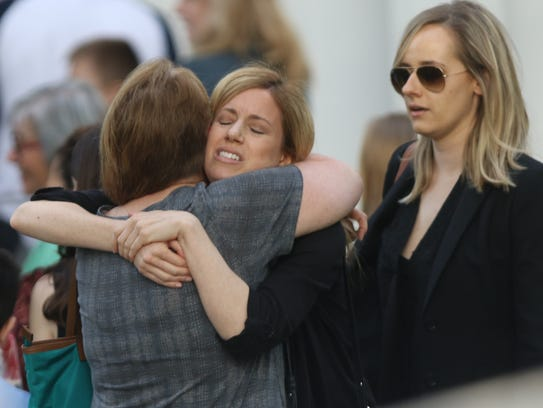 Women hug outside Our Lady of the Visitation Church,