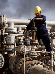Oil personnel work at the Rumaila oil refinery near