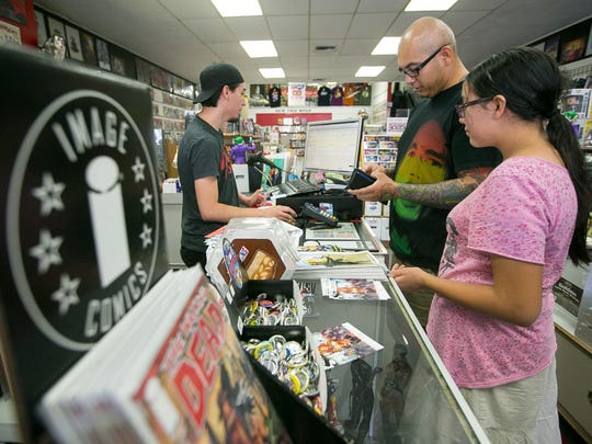 Employee Chris Lopez (left) rings-up Adolph Bohn and his daughter Izabella, 12,  at Drawn to Comics store in downtown Glendale on Friday, June 27, 2014.