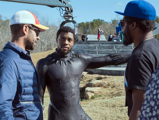 Chadwick Boseman (center) goes over a scene with executive