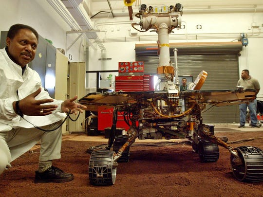 Edward Tunstel Jr., left, a mobility engineer, briefs a reporter about the capability of the Mars rovers Spirit and Opportunity using a full-scale working version, at NASA's Jet Propulsion Laboratory, in Pasadena, California, in 2004.