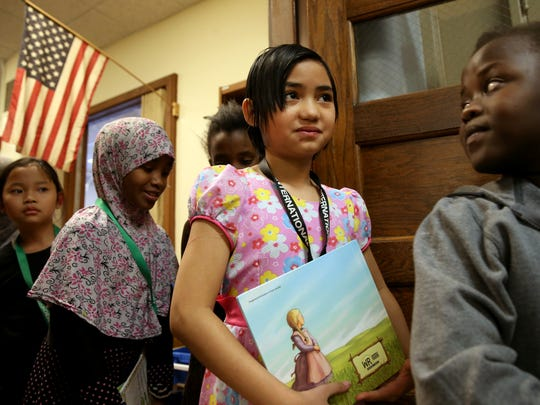 Paw Eh Ler waits with classmates to leave the library with books  at the Rochester International Academy in Rochester.