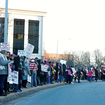 Demonstrators line the sidewalk of South John Q. Hammons