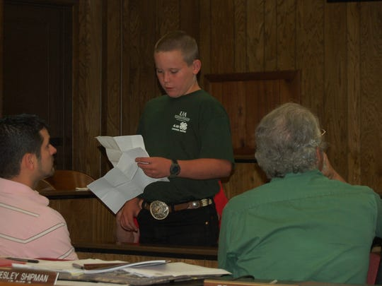 Caleb Rozeboom (standing), the county council president for the Marion County 4-H Club, addresses members of the Marion County Quorum Court on Tuesday night. Justices also heard presentations from Cooperative Extension agents Renee Myers and Brian See and from Christin Dry, the activity director for Creekside Health and Rehab in Yellville.