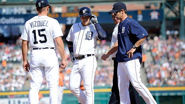 Brad Ausmus checks on Jose Iglesias after he injured his left knee running into first baseman Chris Carter in the third inning.