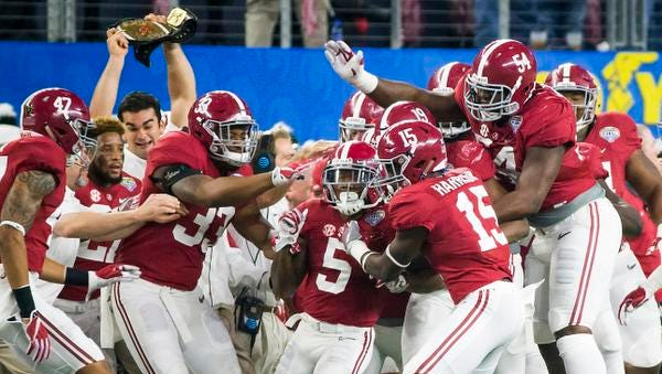 Alabama defensive back Cyrus Jones (5) is mobbed by teammates after intercepting a pass in the end zone during the first half against Michigan State in the Cotton Bowl NCAA college football semifinal playoff game, Thursday, Dec. 31, 2015, in Arlington, Texas. (Smiley N. Pool/The Dallas Morning News via AP)