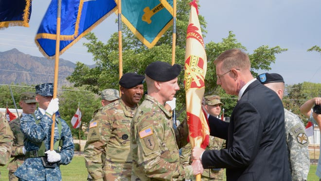 Installation Management Central Region Director Joe C. Capps, right, passes the garrison guidon to incoming WSMR Garrison Commander Col. Dave Brown during the passing of the colors at a Garrison Change of Command ceremony June 7, 2016. Brown will be taking over for Col. Brian Michelson, who served as the installation's garrison commander for three years.