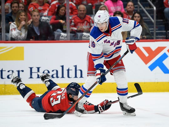 New York Rangers center Ryan Strome (16) skates with the puck past Washington Capitals defenseman Radko Gudas (33), of the Czech Republic, during the second period of an NHL hockey game, Friday, Oct. 18, 2019, in Washington. (AP Photo/Nick Wass)