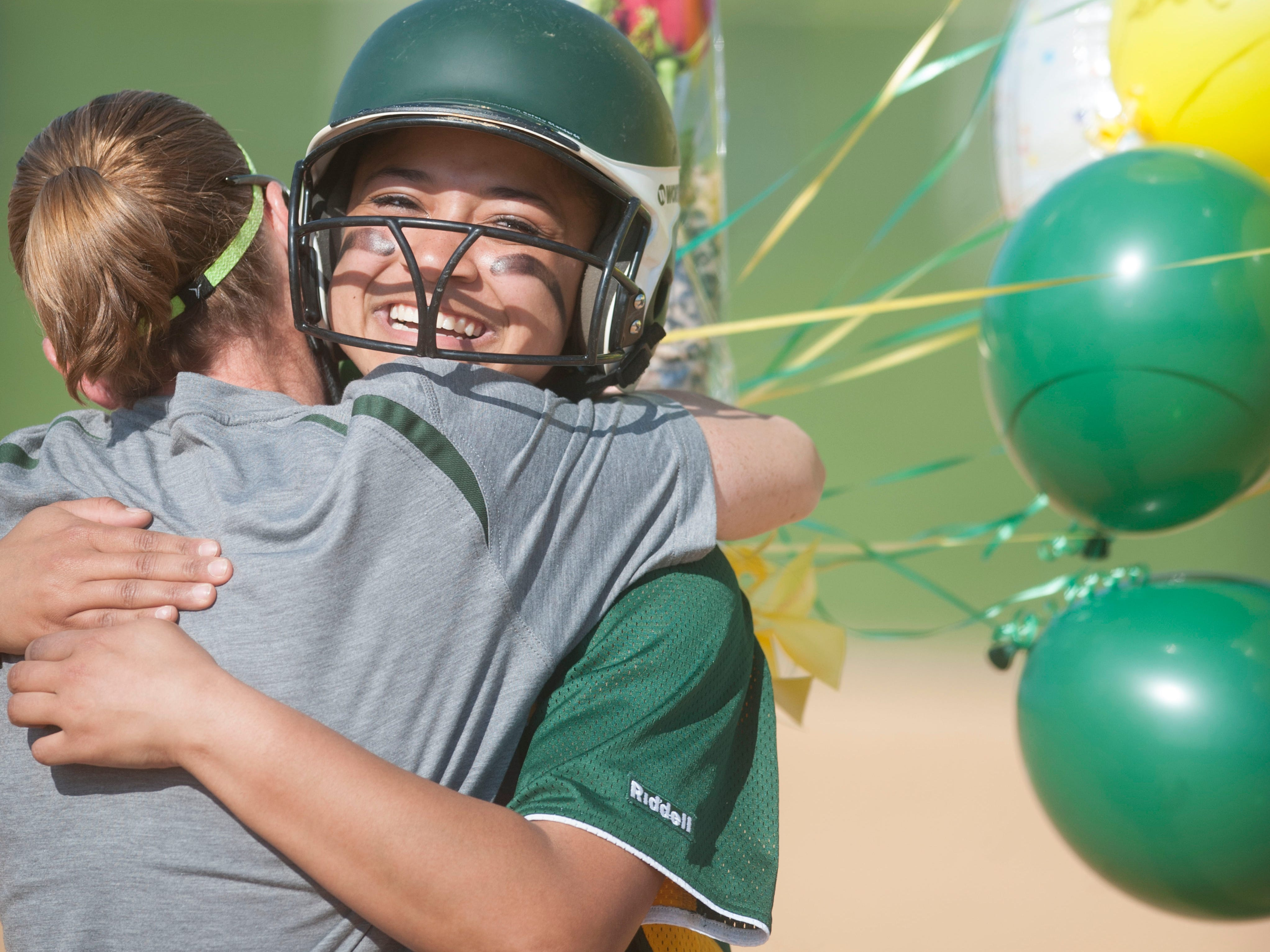 Clearview's Dom Waters, facing, is congratulated by Clearview softball coach Deana Moore after Waters hit her 100th career hit during the 5th inning of Wednesdays softball game between Clearview' and Hammonton played at Clearview High School. 04.29.15