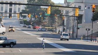 Freezing temperatures in downtown Montgomery meant for light traffic and few pedestrians down a usually busy Dexter Avenue on Thursday, Jan. 8, 2015. Although a few bundled people could be found walking around.