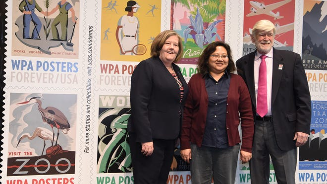 Megan Brennan, left, postmaster general and chief executive officer of the U.S. Postal Service, stands with stamp designer Maribel O. Gray, center, and David Roosevelt, right, grandson of President Franklin D. Roosevelt and Eleanor Roosevelt, during a first-day-of-issue ceremony for 20 stamps of 10 different designs based on Work Projects Administration posters at the Franklin D. Roosevelt Presidential Library and Museum in Hyde Park.
