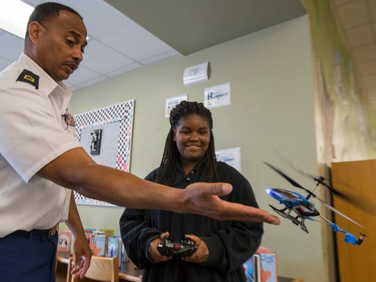 Golden apple winner Jesse Bryson, a JROTC instructor at Fort Myers High School, teaches Eshanti Sanders, 11, a 5th grade student at James Stephens Academy, how to pilot a remote control helicopter Monday, 3/27/17. Bryson and a handful of cadets were visiting elemenatry students at James Stephens Academy, as part of a mentoring program with the academy.