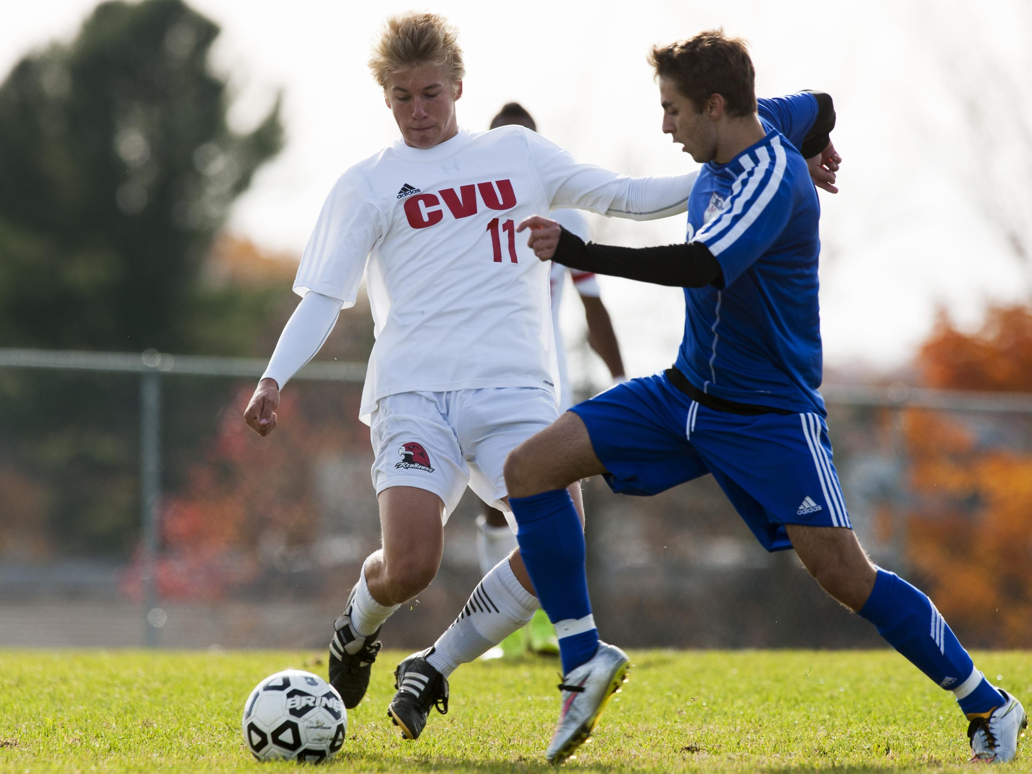 Mount Anthony's Trey Lang (8) battles for the ball with CVU's Kyler White-Hansen (11) during the Division I boys soccer semifinal game.