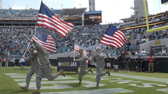 Members of the military run into the field carrying American flags during player introductions before an NFL football game between the Jacksonville Jaguars and the Baltimore Ravens in Jacksonville Sunday.