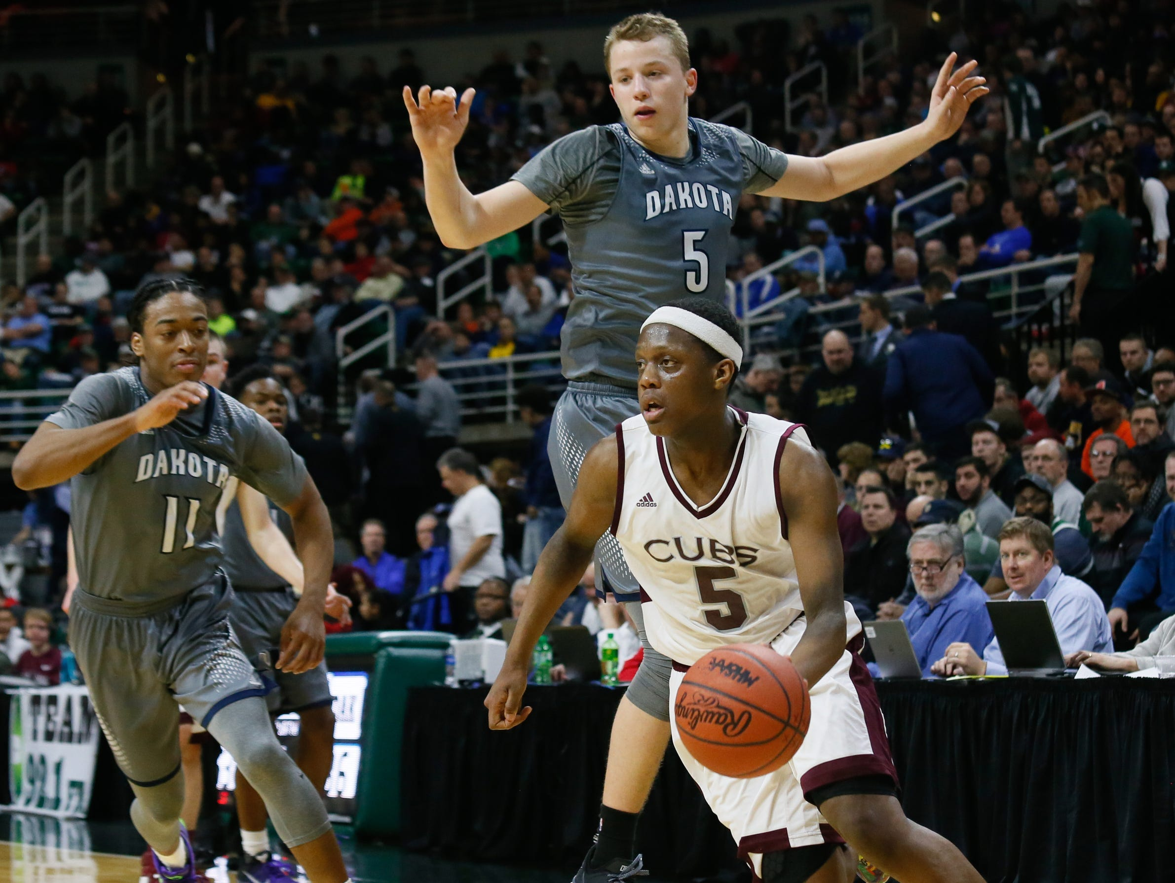 Detroit U-D Jesuit's Cassius Winston dribbles past Macomb Dakota's Thomas Kithier (5) during the 2016 MHSAA boys basketball Class A semifinals at the Breslin Center in East Lansing.